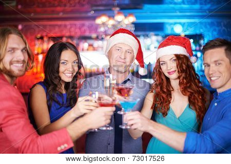 Portrait of boozing people toasting at party and looking at camera