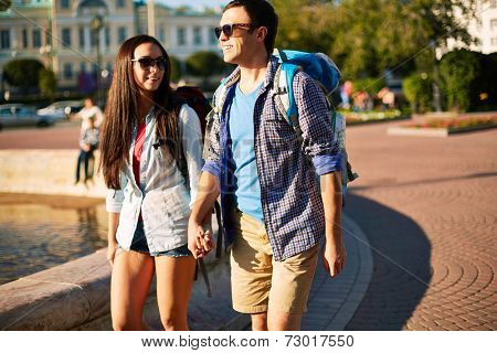 Amorous dates with backpacks taking walk in a city