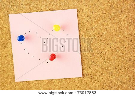 Pink sticker with heart shaped with pinholes on corkboard background