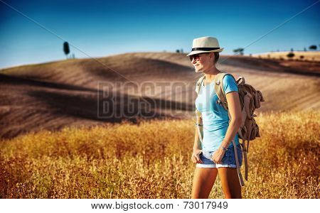 Tourist girl enjoying view of beautiful dry golden wheat hills, traveling along Europe in autumnal season, active lifestyle concept