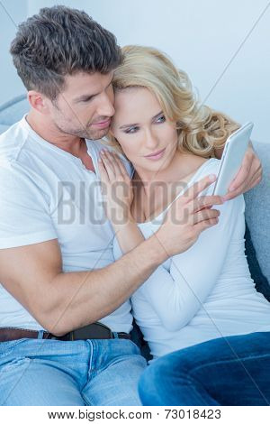 Loving couple reading an sms on a mobile phone as they relax together arm in arm on a sofa at home