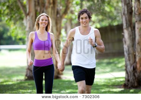 Active Young Couple Holding Hands In Park