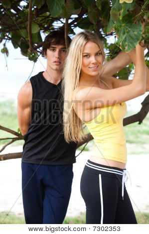 Young Couple Standing Under Tree
