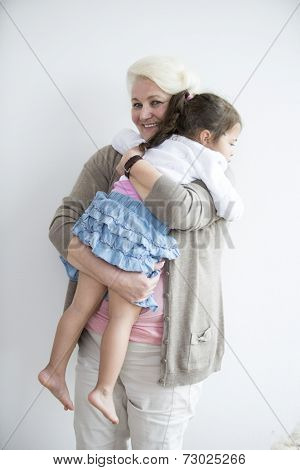 Portrait of happy grandmother carrying granddaughter at home