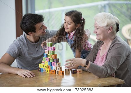 Girl playing with alphabet blocks by father and grandmother at table in house