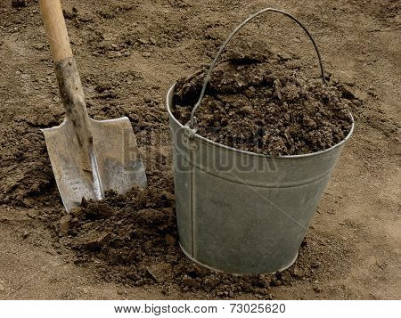 bucket full of soil with spade on dirt background