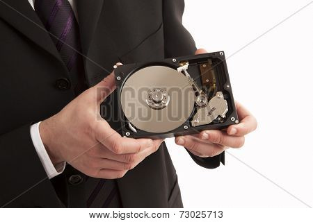 Close-up of person showing physical parts of hard drive on white background