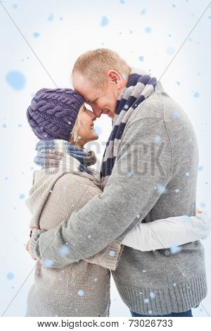 Composite image of Happy mature couple in winter clothes hugging with snow falling