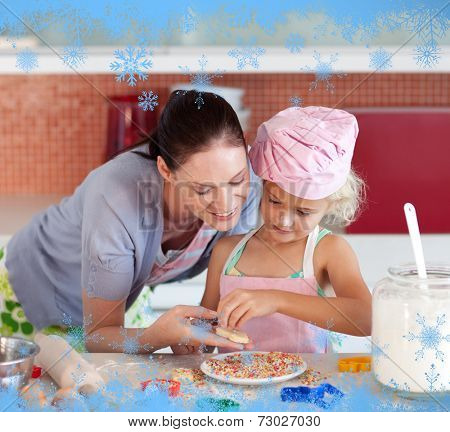 Pretty mother and her daughter baking in a kitchen against snow flake frame in blue