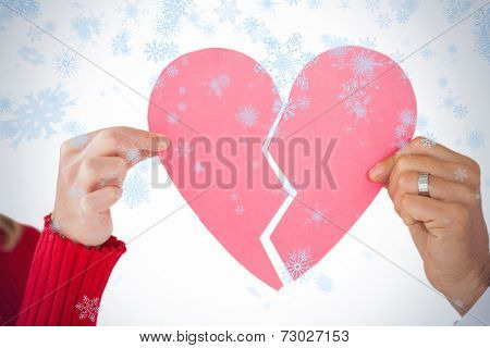 Couple holding two halves of broken heart against snow falling