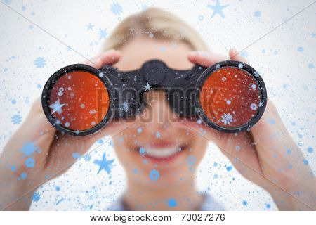 Composite image of woman looking through binoculars against snow falling