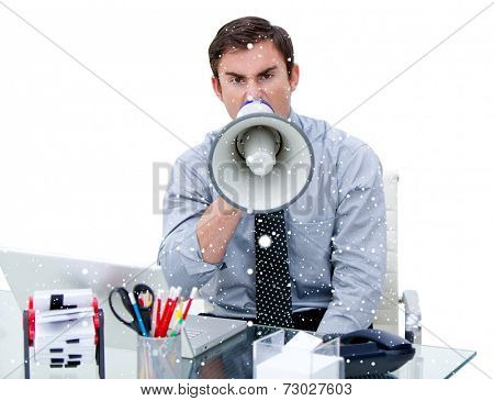 Composite image of Furious businessman yelling through a megaphone sitting at his desk with snow falling