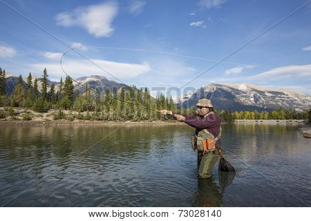 fisherman fly fishing in a mountain river.