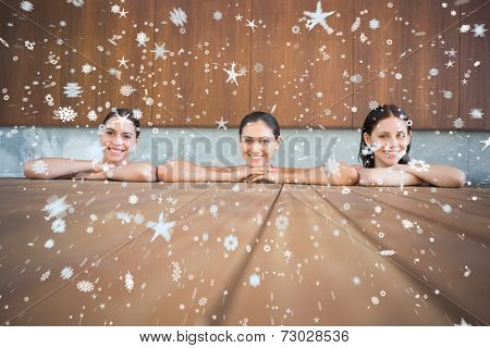 Cheerful young women in swimming pool against snow