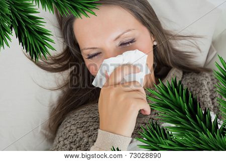 Sick woman lying on sofa and blowing nose against digitally generated fir tree branches