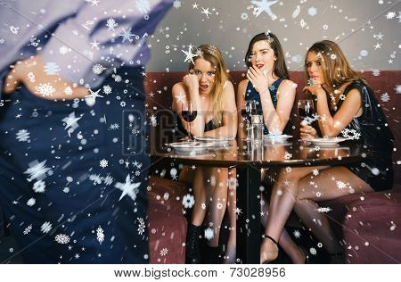 Composite image of Three friends checking out mans rear against snow