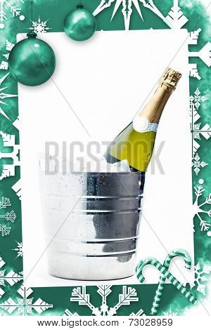 Christmas frame against bottle of champagne chilling in ice bucket