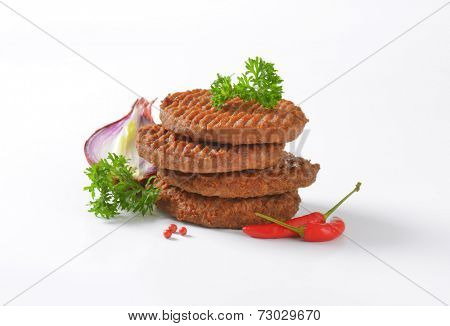 four grilled burgers with vegetable side dish