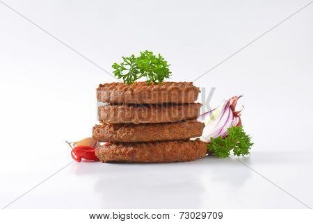 four grilled burgers stacked one on the each other, with vegetable and chili pepper