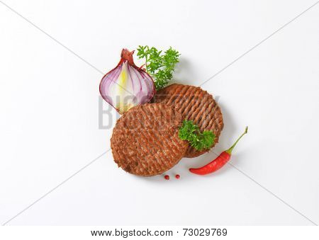 overhead of grilled burgers with vegetable side dish