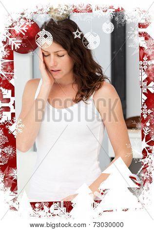 Beautiful woman having a headache in the bathroom against christmas themed frame