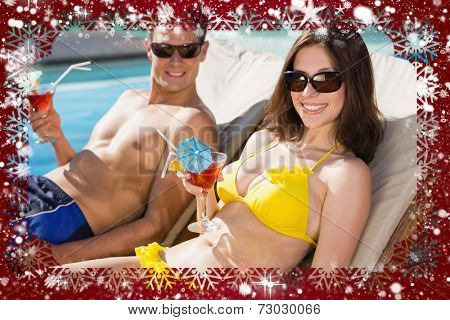 Smiling couple with drinks sitting by swimming pool against snow