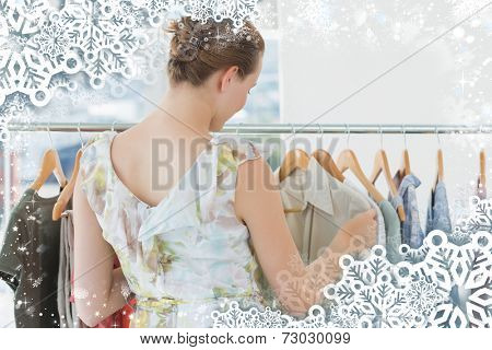 Female customer selecting clothes at clothing rack in store against snow