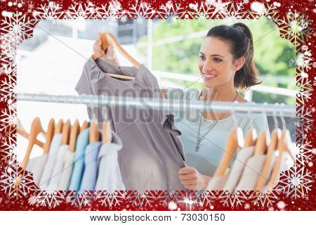 Composite image of fashion woman choosing dress against snow