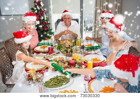 Cheerful family at dining table for christmas dinner against snow falling