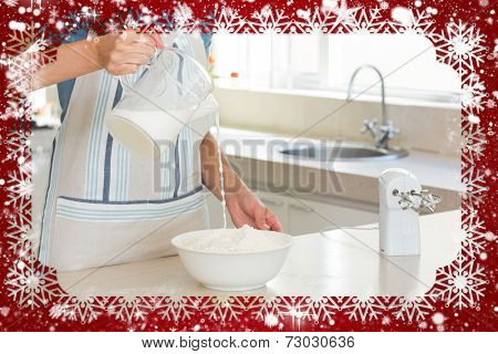 Mid section of woman pouring milk into dough at kitchen against snow