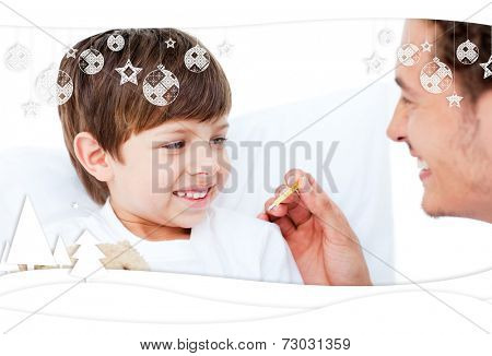 Handsome doctor taking little boys temperature against christmas themed frame