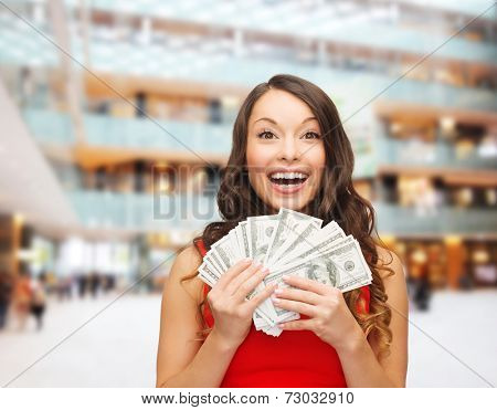 holidays, banking, winning and people concept - smiling woman in red dress with us dollar money over shopping centre background