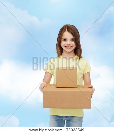 advertising, childhood, delivery, mail and people - smiling little girl holding cardboard boxes over cloudy background