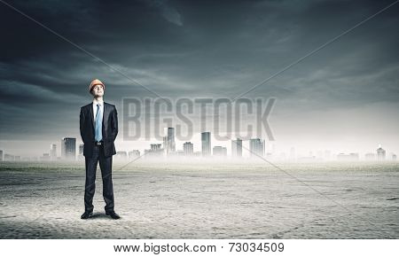 Young man engineer in hardhat against city background