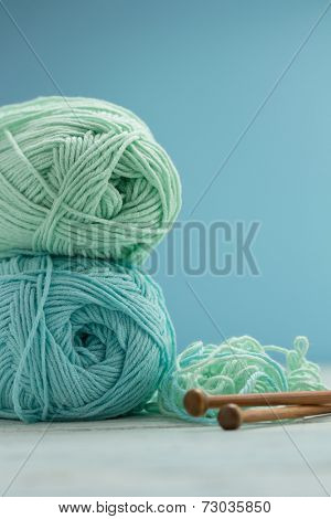 Light blue and green yarn with knitting needles