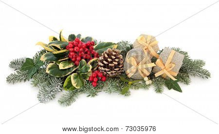 Christmas gift and bauble decorations with holly, ivy, mistletoe, fir and cedar leaf sprigs over white background.