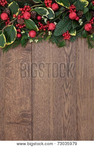 Christmas background border with red bauble bell decorations, holly, mistletoe and fir with pine cones over old oak.