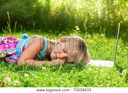 Little girl tired to use laptop and fell asleep in a summer garden
