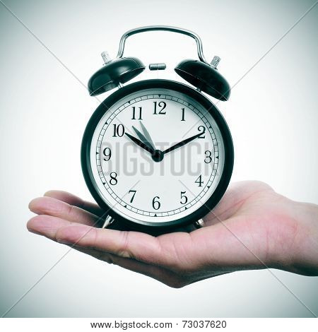 someone holding an alarm clock adjusting backward one hour at the end of the summer time