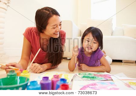 Mother And Daughter Lying On Floor And Painting Picture