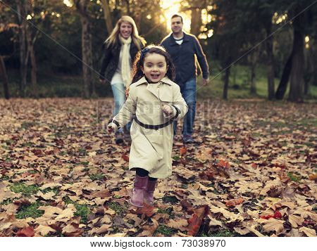 Outdoor portrait of a happy family enjoying the fall season