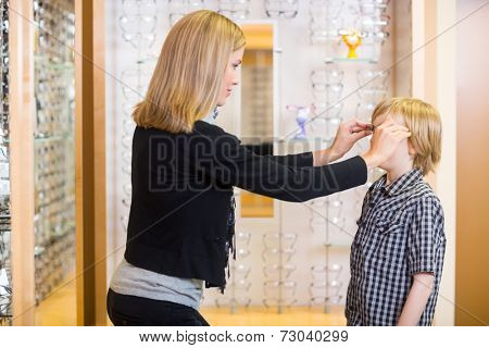 Side view of mid adult woman trying spectacles on son at shop