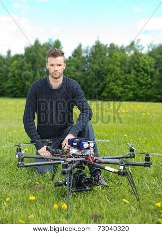 Portrait of confident young technician with UAV drone in park