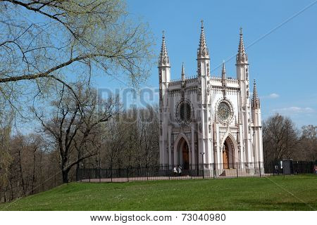 PETERHOF, ST. PETERSBURG, RUSSIA - MAY 9, 2012: People walks around the Gothic chapel in Alexandria garden. The chapel was designed by Karl Friedrich Schinkel in 1829 and consecrated in July 1834