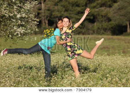 Two Beautiful Young Women Standing In Blooming Meadow