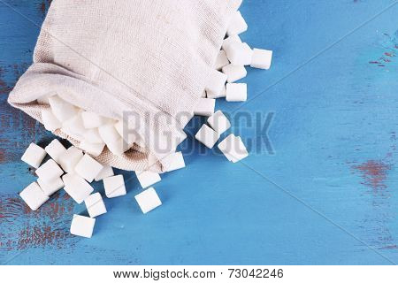 Refined sugar in bag on color wooden background