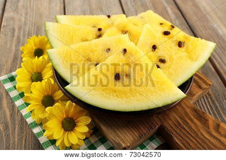 Slices of watermelon on plate on cutting board on checkered napkin and yellow flowers on wooden background