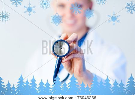 Doctor holding out stethescope with focus on object against snowflakes and fir trees in blue