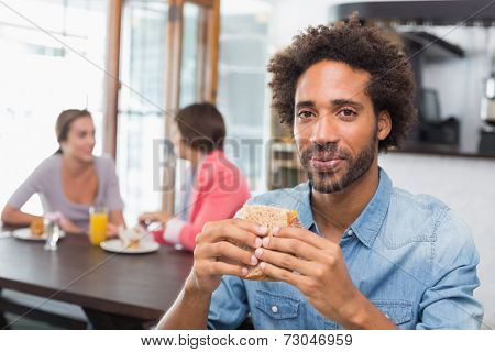 Handsome man eating a sandwich at the coffee shop