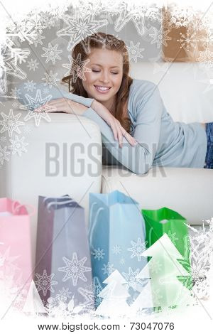 Young woman taking a moment off on her couch after a shopping tour against christmas frame